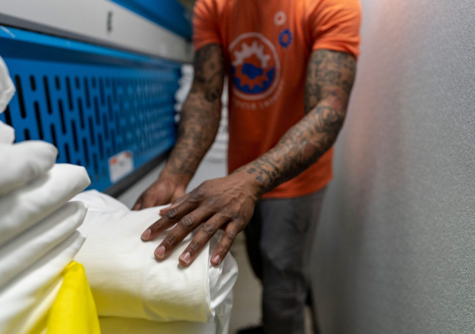 Postindustrial, Javis Williams folds sheets at Wash Cycle Laundry in Philadelphia. He began working at Wash Cycle several weeks ago after being released from jail. Photo by Jessica Kourkounis