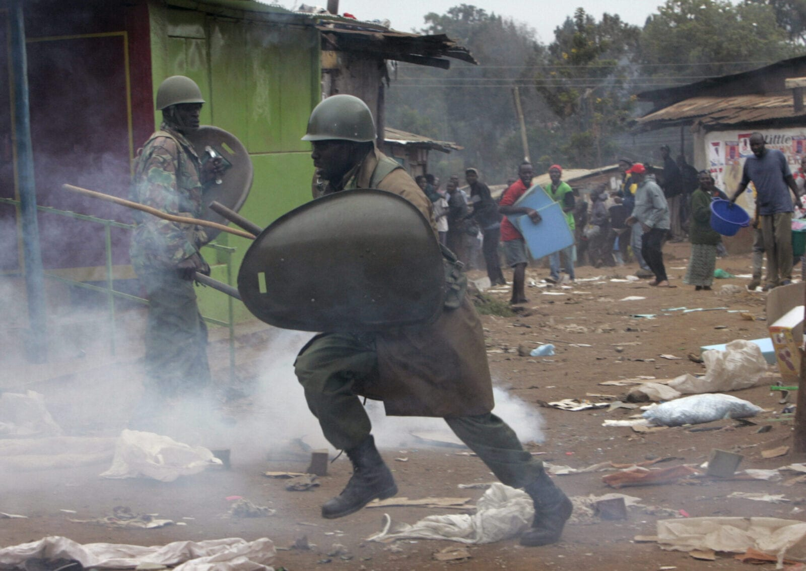 A riot police officer runs away from opposition supporters throwing stones on Monday, Dec. 31, 2007 during riots at the Kibera slum in Nairobi. Police fired shots in the air and sent tear gas into Nairobi's slums Monday as President Mwai Kibaki began a second term after an election marred by violence and allegations that he stole the vote. (AP Photo/Karel Prinsloo)